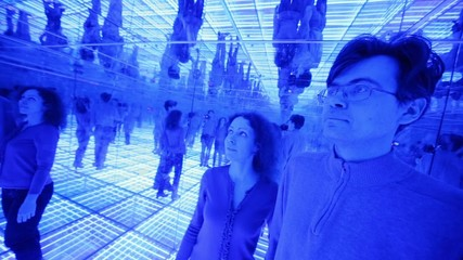 Couple have fun in a mirrored room with blue lights
