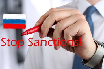 "Man drawing a phrase ""stop  sanctions""  by a  red pen . Flag of"