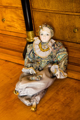 Harlequin doll on an antique cherry wood desk