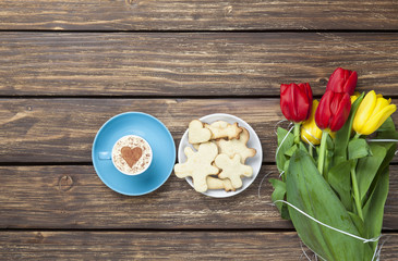 Cup of cappuccino with heart shape and bouquet of tulips with co