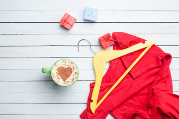 Cup of cappuccino with heart shape and gifts with hanger