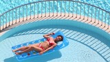 Pretty woman in swimsuit floats on air mattress in outdoor pool