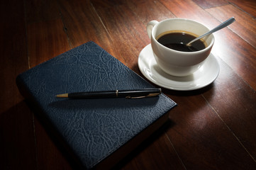 Coffee cup with book and pen.