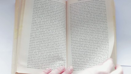 Turning pages of the book by hand, from right to left