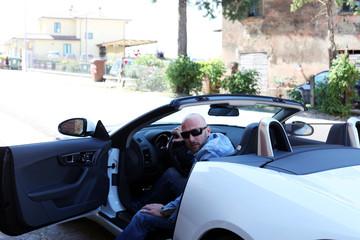 Mann mit weißem Roadster unterwegs