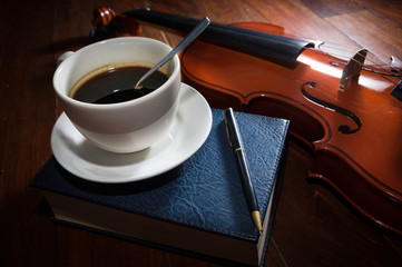 Coffee cup with book,pen and violin.