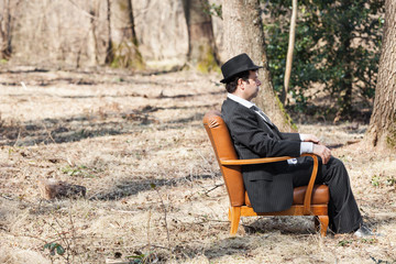 a chair and man in the middle of a forest