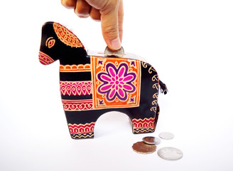 Hand putting a coin in to vintage animal coin bank