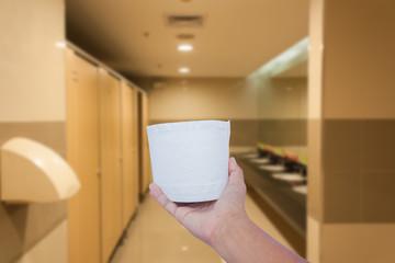 hand hold white toilet paper in latrine