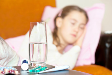 Medicines and glass of water for ill sleeping child.
