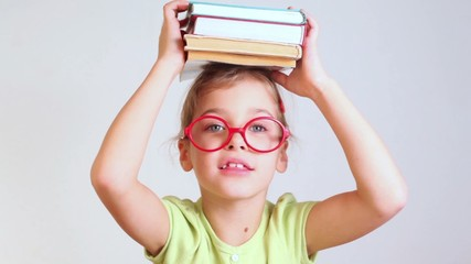 little girl in red glasses speaks with books on a head
