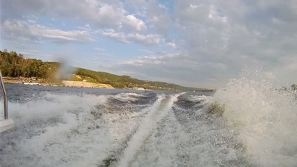 Motorboat quickly floats down river along coastline