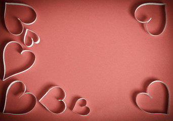 Many hearts of white paper lying on a red background