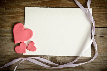 the piece of paper lying with hearts and ribbons on a wooden bac