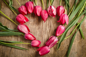 The heart-shaped frame of fresh tulips is laying on an old rusti