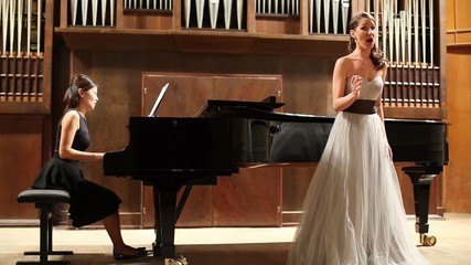 Woman pianist plays the piano and singer sing opera song