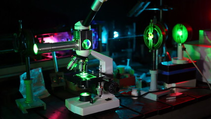 complex of scientific devices from laser, microscope and magnifying glasses on table in dark