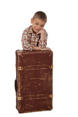 A boy stands near suitcases