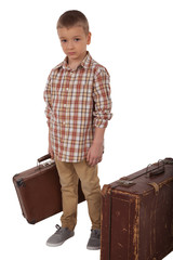 The child stands with two suitcases
