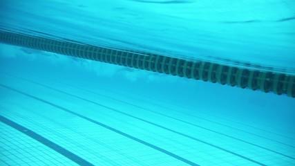 Sportsmen swim by tracks during race in basin, underwater