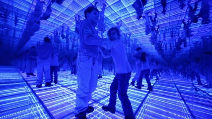 Boy and girl have fun in a mirrored room with blue lights