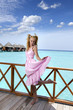 Young beautiful girl stands in pink sundress on sundeck ..