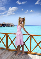 Young beautiful girl in pink sundress on sundeck, Maldives..