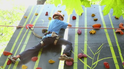 Boy climbs on wall in outdoor climbing center, view from below