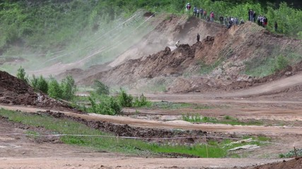 Spectators stands on ground piles and watch several bikers ride buy tracks during motorbike race