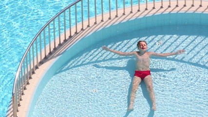 Boy swims lying on his back at padding pool in sunny day
