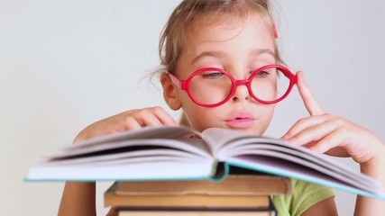 little girl in red glasses reads a book and moves lips