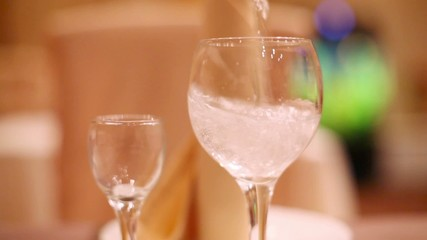 White wine is poured into glass on table in restaurant