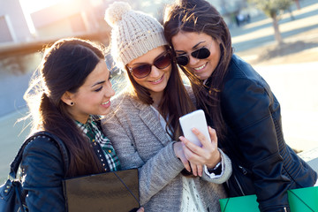 Three students girls using mobile phone in the campus.