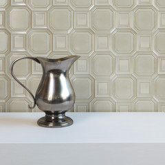 Antique metal pitcher on white table behind tile background
