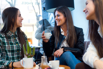 Three young woman drinking coffee and speaking at cafe shop.