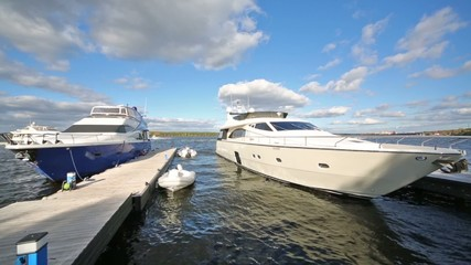 Two beautiful yachts at the pier on river against blue sky