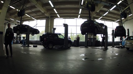 Four cars are fixed on lifting-jack hoist in garage