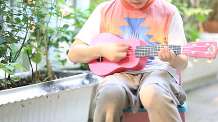 little asian child sitting on mini chair and playing guitar
