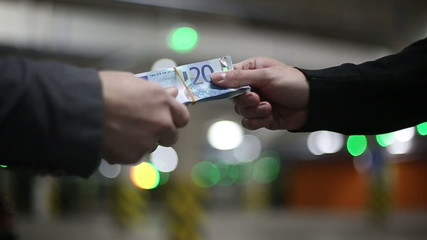Men pass each other money euro banknotes and shake hands.