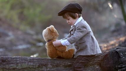 Adorable little boy with teddy bear, having fun