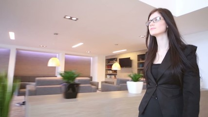 woman in suit goes in waiting hall of business center