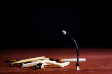 one burned match standing and many burned matches lying