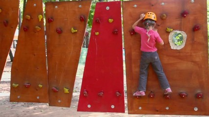 Little girl climbs on pendant wall in outdoor climbing center
