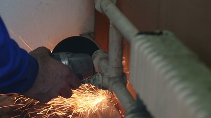 Male hands grinds slice of radiators by angle grinder.