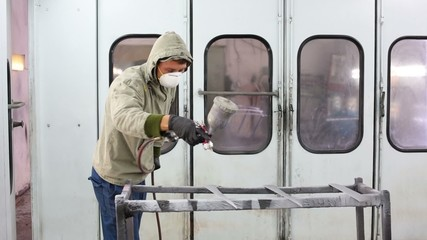 Man in protective clothes and respirator paints car details