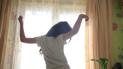 Teen girl stretches awake standing at window silhouette spin