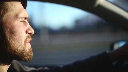 A man drives a car at sunset