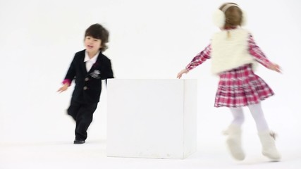 Little pretty boy and girl run around large cube in white studio