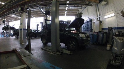 Car stands with lifted cowl in car-care center