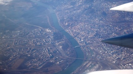 View at city from an aircraft window at sunny day.